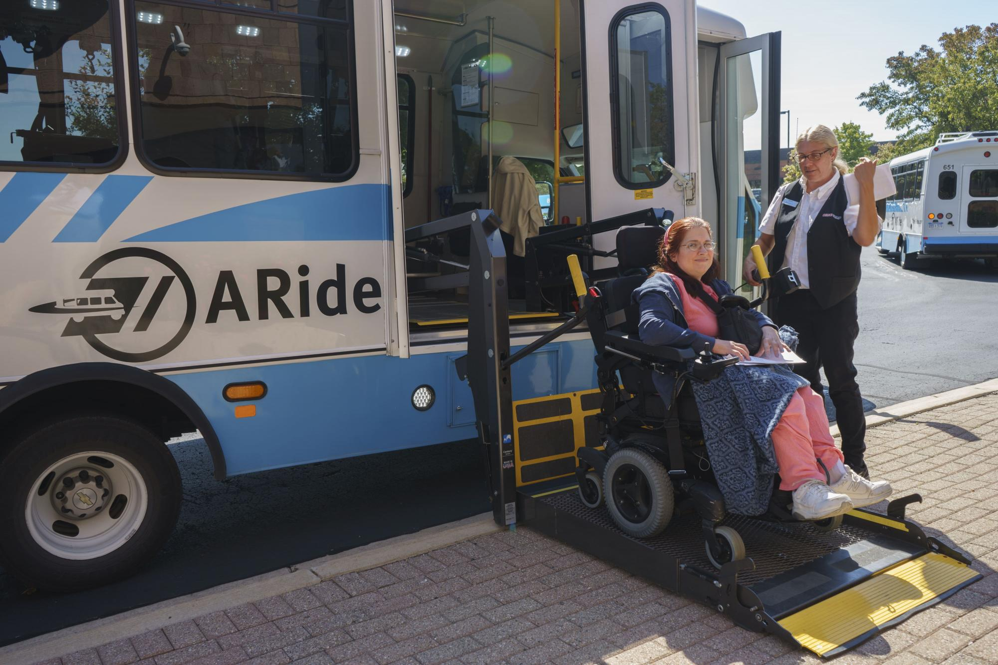 A woman has help boarding the A-Ride bus with her wheelchair.