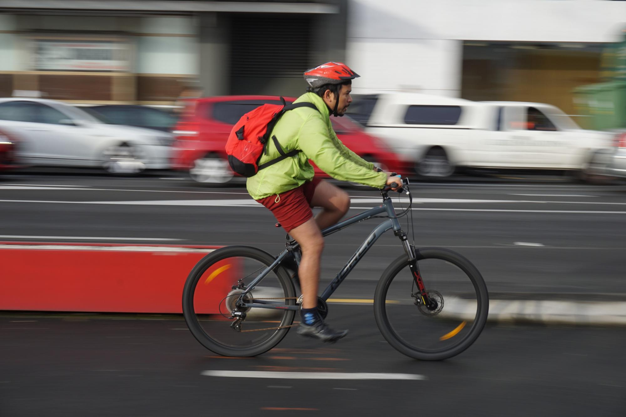 Man riding a bike in a road with cars behind him