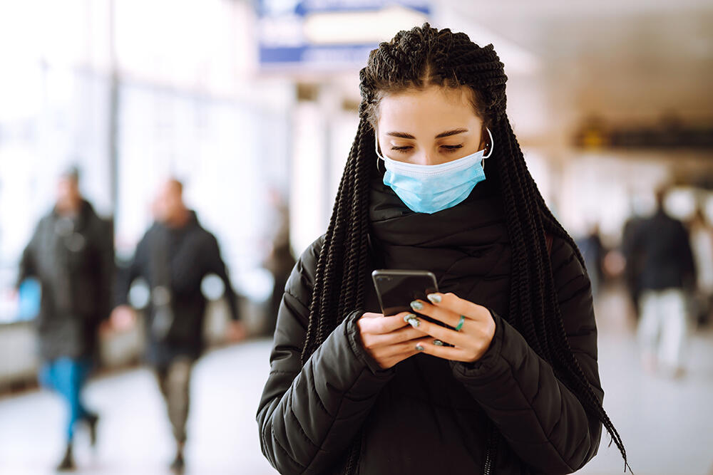 woman wearing mask looking at phone inside building