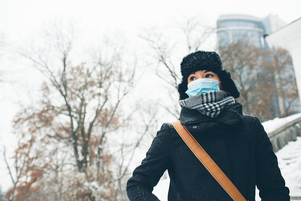 woman wearing mask winter coat on campus
