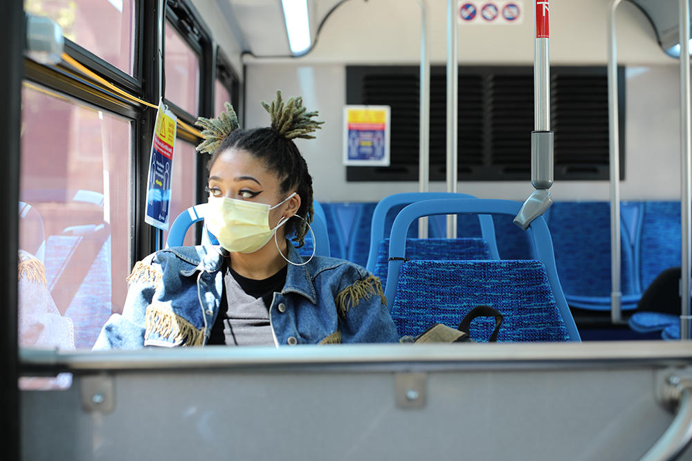 African American woman wearing mask riding bus