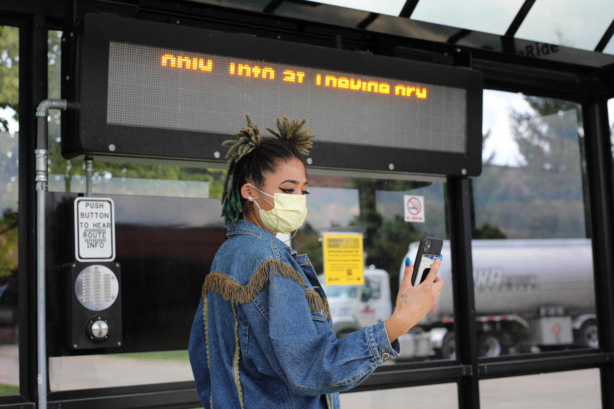Woman looking at phone at bus stop