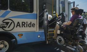 A passenger in a wheelchair is lifted up to ride on the A-Ride bus.