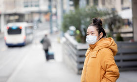 Asian woman wearing mask waiting for bus