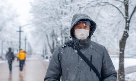 man wearing mask winter coat walking in snow